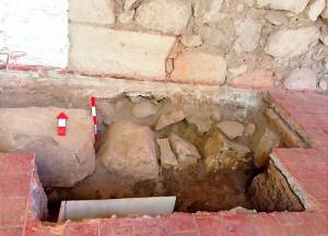 Parte de la excavación en la que se pueden apreciar los bolones cercados por un muro de piedras grandes, a pocos centímetros de la superficie.