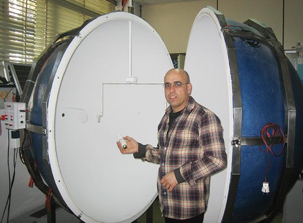 Félix García Rosillo ante una esfera integradora abierta y preparada para la medida de flujo luminoso.