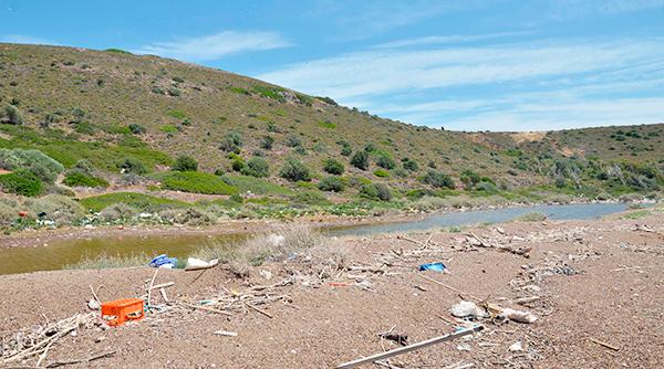 Acumulación de residuos antropogénicos (muchos de ellos de plástico) entre fragmentos naturales en las costa de una pequeña isla del Golfo de Corinto.